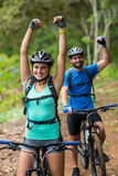 Athletic couple standing with mountain bike in forest Stock Images