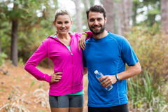 Athletic couple standing together in forest Royalty Free Stock Image