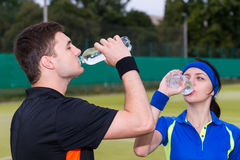 Athletic couple of tennis players drinking water after match out Royalty Free Stock Photo