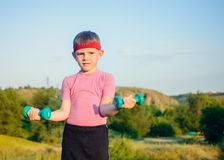 Athletic Cute Boy Lifting Two Small Dumbbells Royalty Free Stock Photography