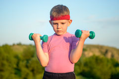 Athletic Cute Boy Lifting Two Small Dumbbells Royalty Free Stock Images