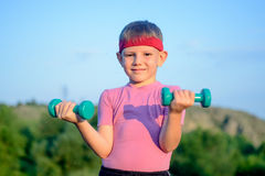 Athletic Cute Boy Lifting Two Small Dumbbells Royalty Free Stock Image