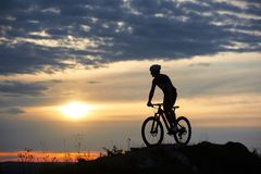 Athletic cyclist in helmet standing on bike and posing in twilight. stock images
