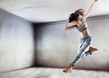 Athletic dancer jumping on a concrete wall background Royalty Free Stock Image