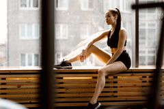 Athletic dark-haired  girl dressed in black sports top and shorts is sitting on a wooden window sill in the gym royalty free stock photo