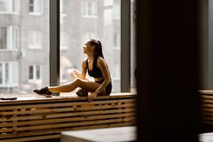 Athletic dark-haired  girl dressed in black sports top and shorts is sitting on a wooden window sill in the gym stock photography
