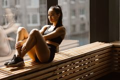 Athletic dark-haired  girl dressed in black sports top and shorts is sitting on a wooden window sill in the gym royalty free stock photography