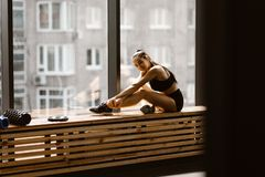 Athletic dark-haired  girl dressed in black sports top and shorts is sitting on a wooden window sill in the gym royalty free stock images