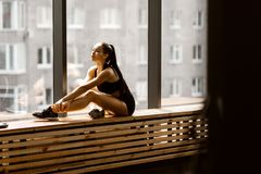 Athletic dark-haired  girl dressed in black sports top and shorts is sitting on a wooden window sill in the gym stock photos
