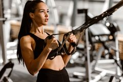 Athletic dark-haired  girl dressed in black sports top and shorts is working out on the fitness-station in the gym stock images