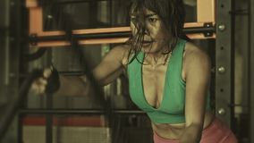 Athletic and determined Asian Indonesian sport woman working hard training sweaty at gym a battle ropes workout. Close up grunge shot of young athletic and stock footage