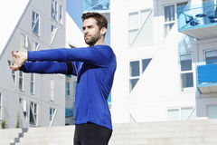 Athletic dude stretching. In sports clothing Stock Image