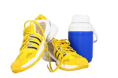 Athletic Equipment. Bright yellow athletic shoes and a blue water jug on a white background Stock Images