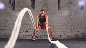 Athletic female actively in a gym exercises with battle ropes during her cross fitness workout. slow motion