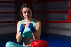 Athletic female boxer sitting and clenching her fists Royalty Free Stock Photo