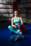 Athletic female boxer sitting near lying boxing gloves and helme Stock Photos