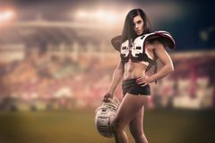 Athletic female dressed as an American Football Player. Real uniform, helmet, pads, ball. Athletic female dressed as an American Football Player at the stadium royalty free stock photography