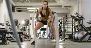 Athletic female high-intensity interval training using battle ropes. Beautiful fit athletic female working out using battle ropes. High-intensity interval stock footage