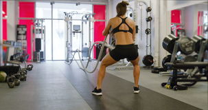 Athletic female high-intensity interval training using battle ropes stock video