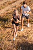 Athletic female runner and male fitness model running together. Outdoors royalty free stock images