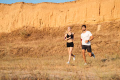 Athletic female runner and male fitness model running together. Outdoors stock image