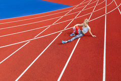 Athletic female runner rests on running track at sports arena Stock Photography