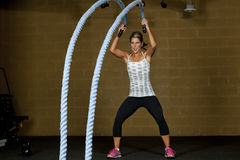 Athletic Female Trainers. An attractive young and athletic girl using training ropes in a gym Royalty Free Stock Photos