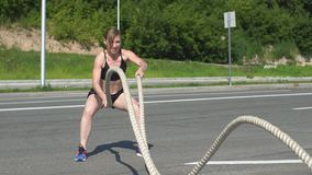 Athletic female working out using battle ropes. Crossfit stock video