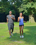 Athletic and fit African American couple - jogging in a park Stock Photos