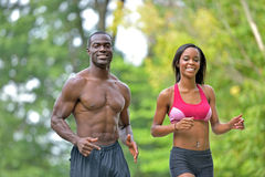 Athletic and fit African American couple - jogging in a park. Cute African-American couple working out together in park - jogging - male shirtless and women in Royalty Free Stock Image