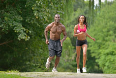 Athletic and fit African American couple - jogging in a park Royalty Free Stock Photo