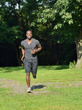 Athletic and fit African American male - jogging in a park Royalty Free Stock Images