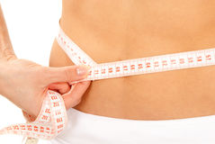 Athletic fit female measuring around her waist stock images