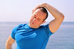Athletic fit runner doing stretching exercise, preparing for morning workout on a seashore. A handsome fitness athlete doing a neck stretching routine in the Stock Photos