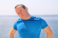 Athletic fit runner doing stretching exercise, preparing for morning workout on a seashore. A handsome fitness athlete doing a neck stretching routine in the Stock Image