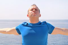 Athletic fit runner doing stretching exercise, preparing for morning workout on a seashore. A handsome fitness athlete doing a neck stretching routine in the Royalty Free Stock Photography