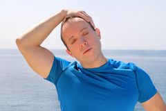 Athletic fit runner doing stretching exercise, preparing for morning workout on a seashore. A handsome fitness athlete doing a neck stretching routine in the Royalty Free Stock Photo