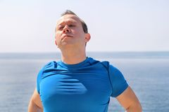 Athletic fit runner doing stretching exercise, preparing for morning workout on a seashore. A handsome fitness athlete doing a neck stretching routine in the Stock Images