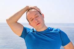 Athletic fit runner doing stretching exercise, preparing for morning workout on a seashore. A handsome fitness athlete doing a neck stretching routine in the Royalty Free Stock Photos