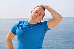 Athletic fit runner doing stretching exercise, preparing for morning workout on a seashore. A handsome fitness athlete doing a neck stretching routine in the Stock Photography