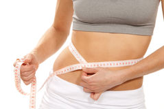 Athletic fit slim female measuring her waist stock photography