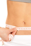 Athletic fit slim female measuring her waist Stock Photo