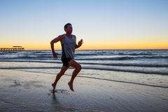 Athletic fit and strong runner man training on Summer sunset beach in sea shore running and fitness workout in sport and healthy l. Portrait of young athletic Stock Photography