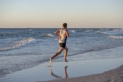 Athletic fit and strong runner man training on Summer sunset beach in sea shore running and fitness workout in sport and healthy l. Back portrait of young Stock Photos