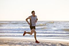 Athletic fit and strong runner man training on Summer sunset beach in sea shore running and fitness workout in sport and healthy l. Portrait of young athletic Royalty Free Stock Photo