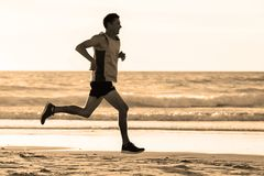 Athletic fit and strong runner man training on Summer sunset beach in sea shore running and fitness workout in sport and healthy l. Portrait of young athletic Royalty Free Stock Image