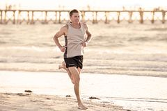 Athletic fit and strong runner man training on Summer sunset beach in sea shore running and fitness workout in sport and healthy l. Portrait of young athletic Royalty Free Stock Photos