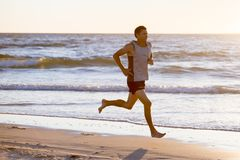 Athletic fit and strong runner man training on Summer sunset beach in sea shore running and fitness workout in sport and healthy l. Portrait of young athletic Royalty Free Stock Images