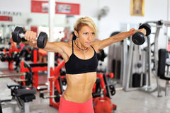 Athletic fit woman training shoulders at the gym Stock Photos