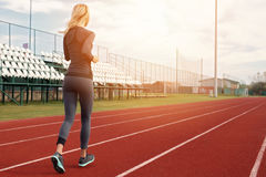 Athletic fitness fit woman running on stadium. Sport, jogging, healthy life style concept Royalty Free Stock Photo